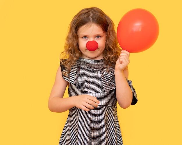 Vue de face fille tenant un ballon rouge