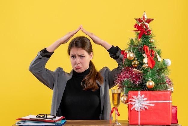 Vue de face fille triste assise au bureau tenant la main au-dessus de la tête comme une maison sur le toit près de l'arbre de noël et des cadeaux cocktail
