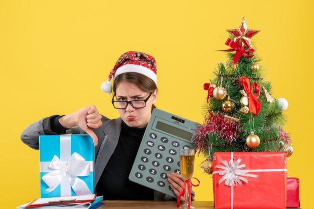 Vue de face fille triste avec chapeau de noël assis à la table faisant le pouce vers le bas signe arbre de noël et cadeaux cocktail