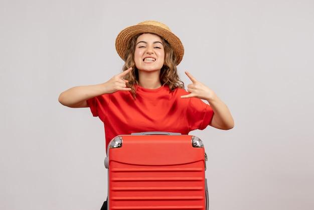 Vue de face de la fille de vacances avec sa valise faisant signe de roche debout sur un mur blanc