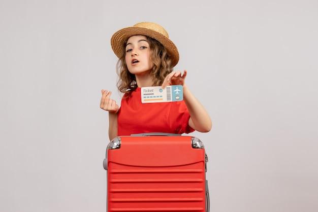 Vue de face de la fille de vacances avec sa valise tenant un billet faisant signe d'argent