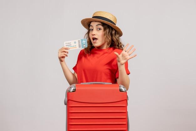 Vue de face de la fille de vacances avec valise rouge tenant un billet de voyage