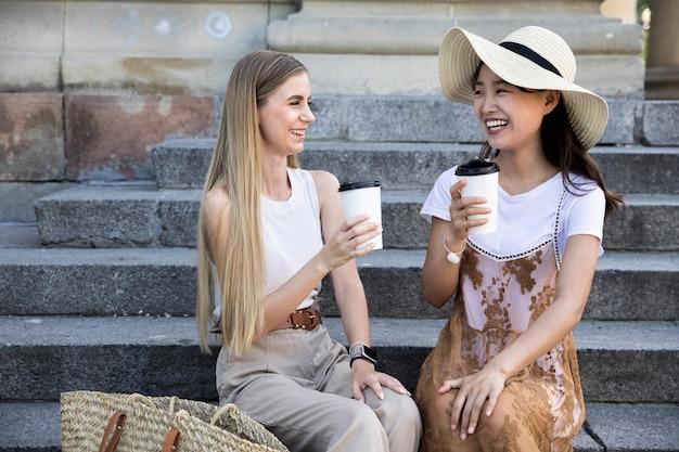 Vue de face des filles ayant une tasse de café