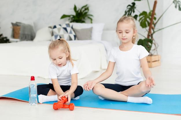 Vue de face des filles exerçant à la maison sur un tapis de yoga