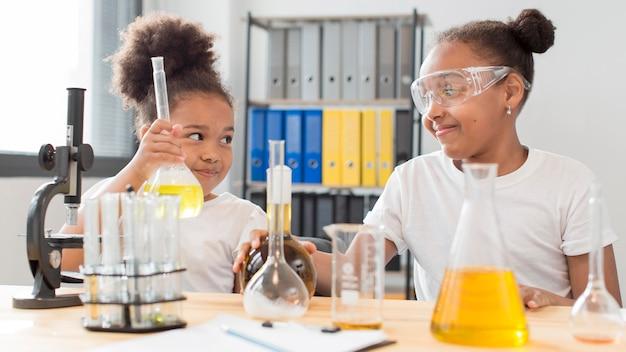 Vue de face de filles scientifiques à la maison expérimenter la chimie