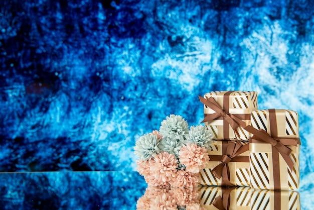 Vue de face des fleurs de cadeaux de mariage reflétées sur un miroir sur fond bleu glace