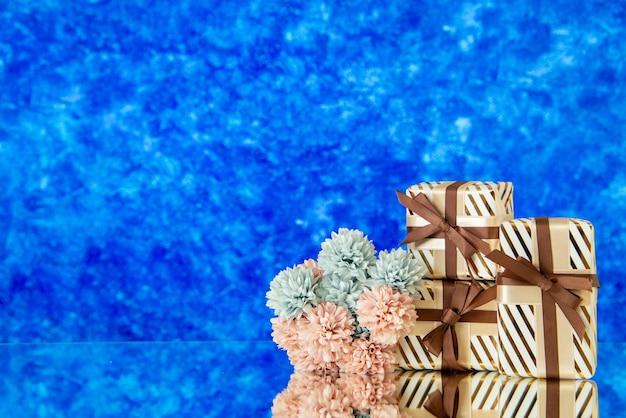 Vue de face des fleurs de cadeaux de vacances reflétées sur un miroir sur fond bleu flou