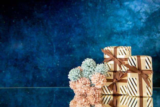 Vue de face des fleurs de cadeaux de vacances reflétées sur un miroir sur fond bleu foncé avec lieu de copie