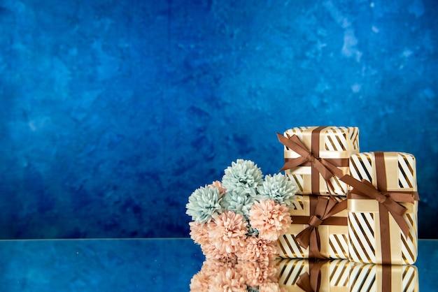 Vue de face des fleurs de cadeaux de vacances reflétées sur un miroir sur fond bleu foncé