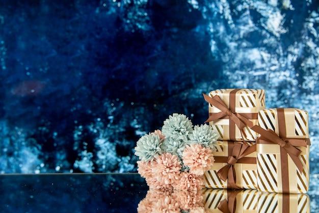 Vue de face des fleurs de cadeaux de vacances reflétées sur un miroir sur fond bleu glace