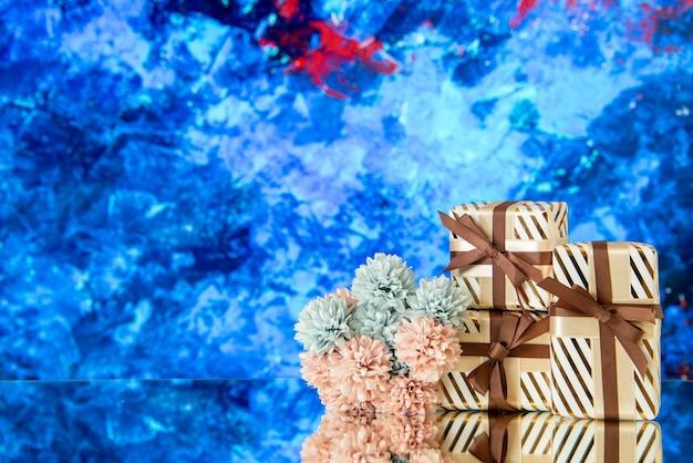 Vue de face des fleurs de cadeaux de vacances reflétées sur un miroir sur fond bleu
