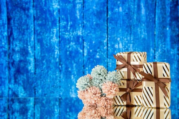 Vue de face des fleurs de cadeaux de vacances reflétées sur un miroir sur fond de bois bleu