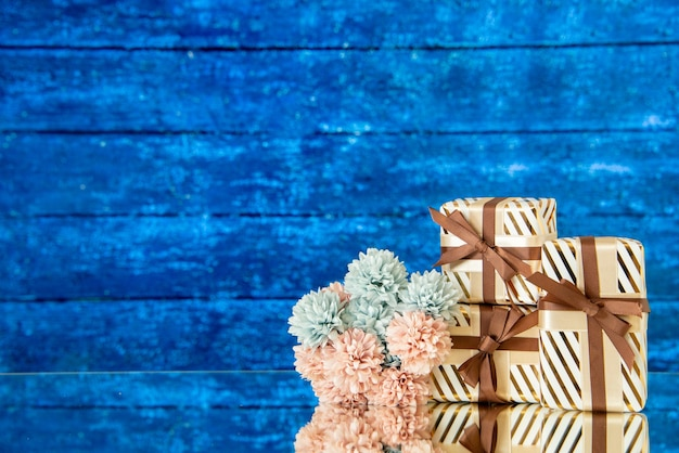 Vue de face des fleurs de cadeaux de vacances reflétées sur le miroir sur le lieu de copie de fond bleu foncé