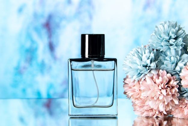 Vue de face des fleurs colorées de parfum élégant sur fond bleu flou