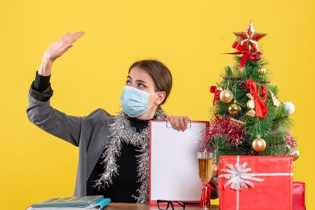 Vue de face forte jeune fille avec masque médical assis à la table levant sa main arbre de noël et cadeaux cocktail