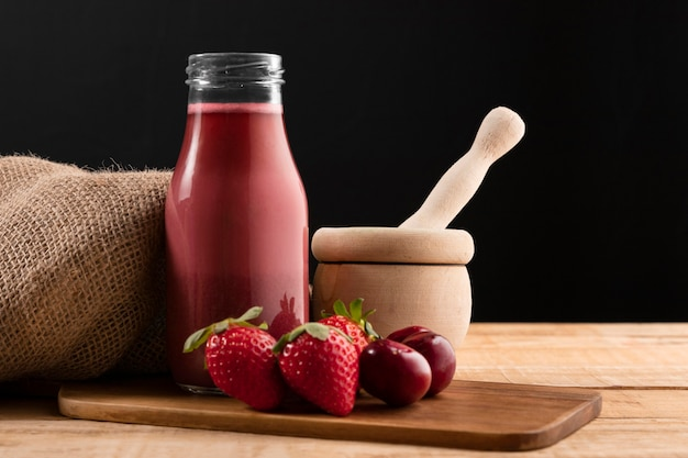 Vue de face fraises et cerises avec smoothie