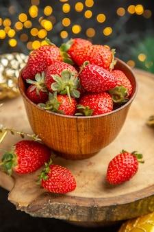 Vue de face des fraises fraîches autour des jouets de noël sur fond sombre goût de fruits photo de noël sombre