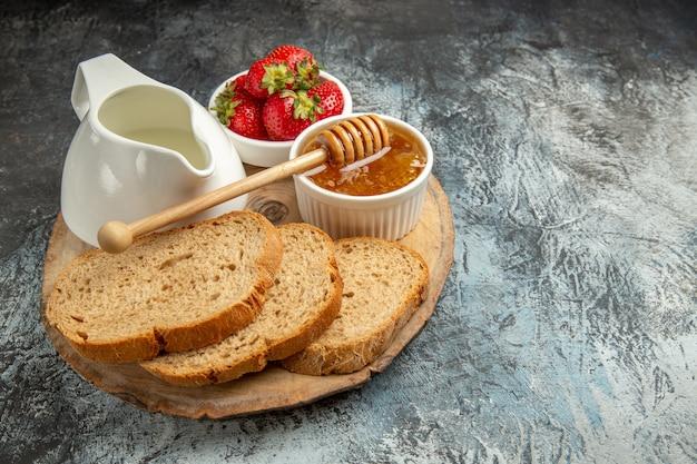 Vue de face fraises fraîches avec du pain et du miel sur la surface sombre de la gelée sucrée de fruits