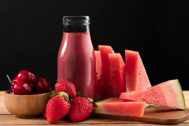 Vue de face fraises et pastèque avec smoothie