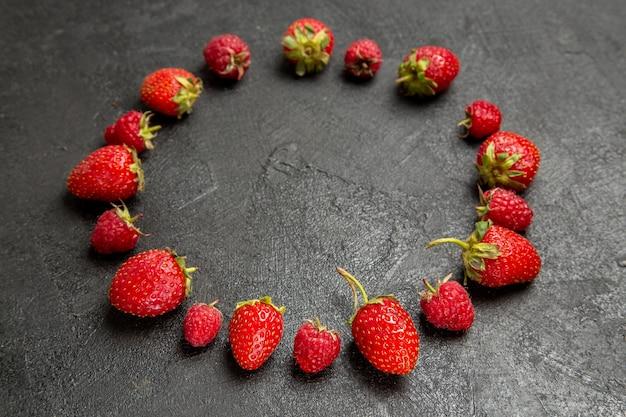 Vue de face fraises rouges fraîches bordées sur fond gris foncé