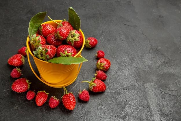 Vue de face fraises rouges fraîches bordées sur fond sombre