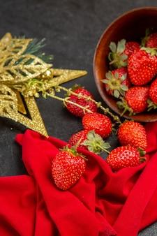 Vue de face des fraises rouges fraîches à l'intérieur de la plaque avec un jouet sur la couleur de fond sombre de nombreux fruits photo moelleux