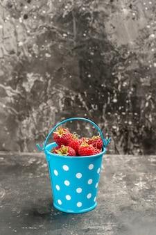 Vue de face de framboises rouges fraîches à l'intérieur d'un petit panier sur une baie de photo sauvage de canneberge aux fruits gris