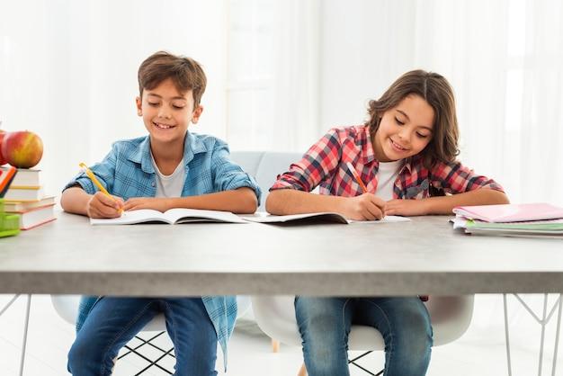 Vue de face des frères et sœurs faisant leurs devoirs ensemble