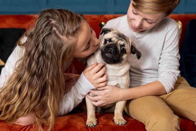 Vue de face frères et sœurs passant du temps avec leur chien