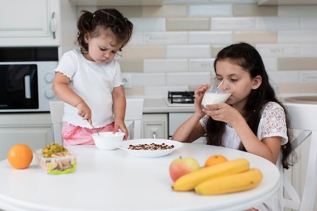 Vue de face des frères et sœurs prenant son petit déjeuner