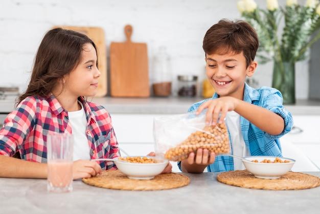 Vue de face des frères et sœurs prépare le petit déjeuner