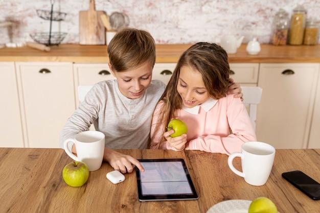 Vue de face frères et sœurs regardant ensemble sur leur tablette