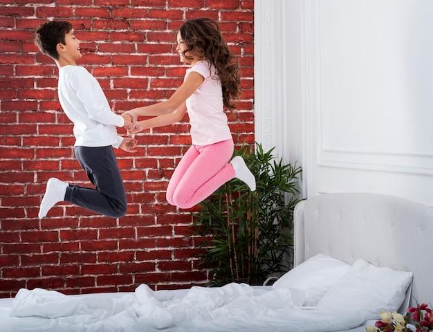 Vue de face des frères et sœurs sautant sur le lit
