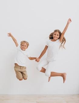 Vue de face des frères et soeurs souriants sautant