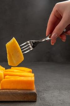 Vue de face fromage frais tranché sur fourchette couleur foncé collation photo petit déjeuner chips repas