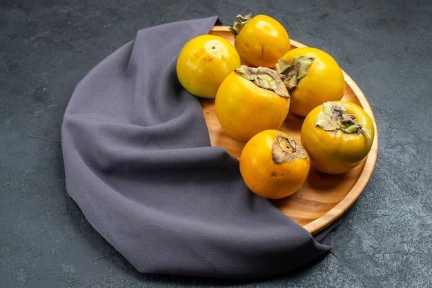 Vue de face de fruits doux mûrs kaki frais sur fond sombre