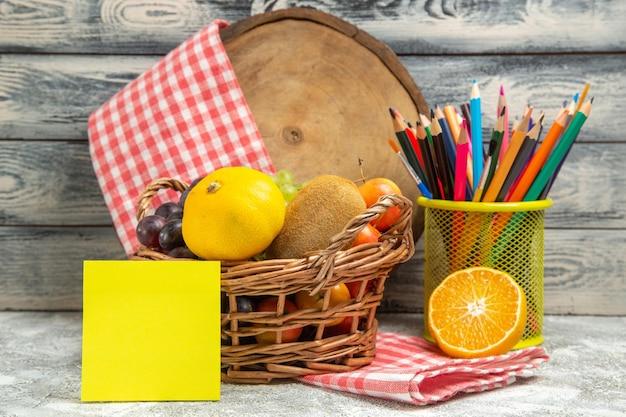 Vue de face des fruits frais avec autocollant et crayons sur fond gris, couleur du cahier d'agrumes de fruits