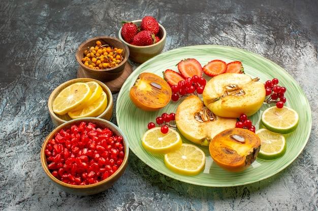 Vue de face fruits frais coings citrons et autres fruits sur table lumineuse couleur fruits frais
