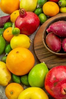 Vue de face fruits frais différents fruits mûrs et moelleux sur fond blanc couleur baies régime santé savoureux