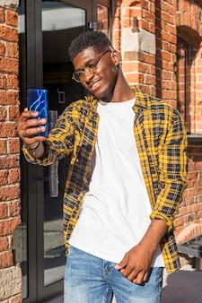 Vue de face garçon adolescent prenant un selfie