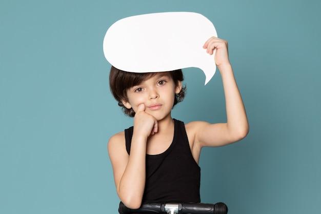Une vue de face garçon mignon adorable doux tenant une pancarte blanche en t-shirt noir sur l'espace bleu