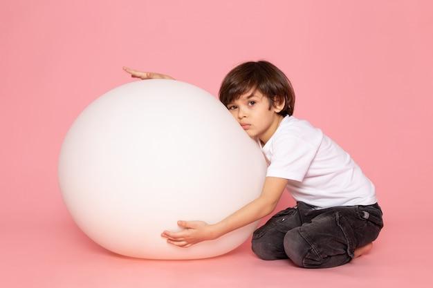 Une vue de face garçon mignon en t-shirt blanc jouant avec la balle blanche sur l'espace rose