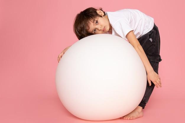 Une vue de face garçon mignon en t-shirt blanc jouant avec une balle ronde blanche sur le sol rose