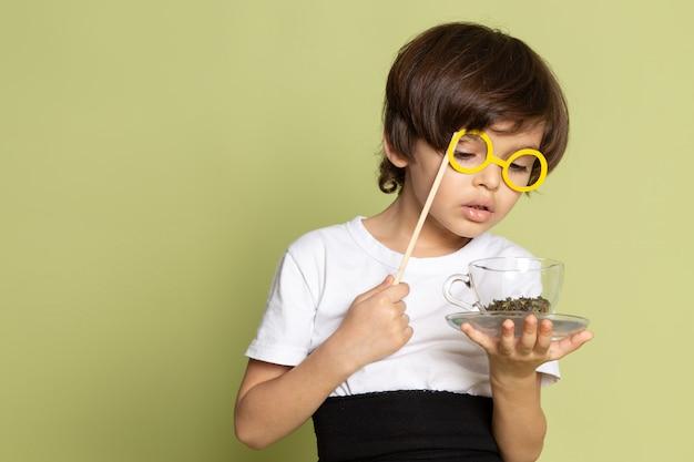 Une vue de face garçon mignon en t-shirt blanc tenant du café sur le sol de couleur pierre
