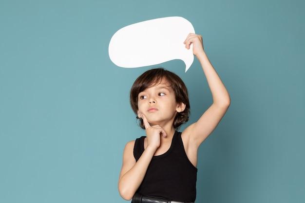 Une vue de face garçon mignon tenant une pancarte blanche en t-shirt noir sur l'espace bleu