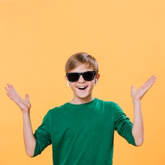 Vue de face d'un garçon moderne avec des lunettes de soleil