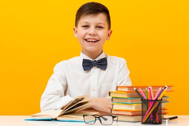 Vue de face garçon souriant avec des livres