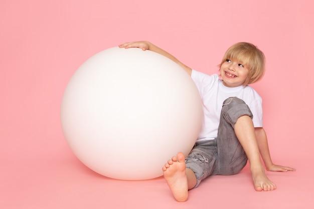 Une vue de face garçon souriant en t-shirt blanc jouant avec une balle ronde blanche sur le sol rose