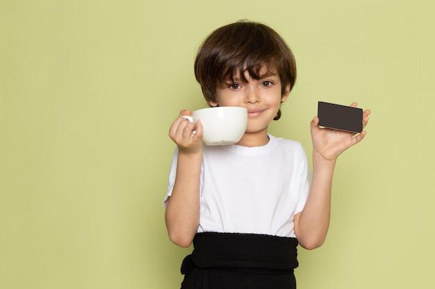 Une vue de face garçon souriant tenant une carte noire et une tasse blanche sur le bureau de couleur pierre