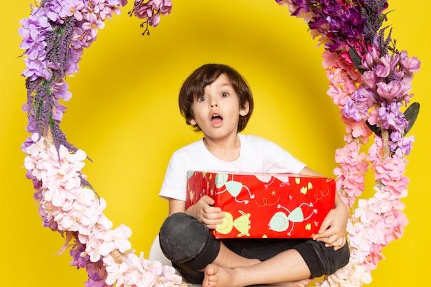 Une vue de face garçon surpris avec rouge conçu présent en t-shirt blanc sur le sol jaune